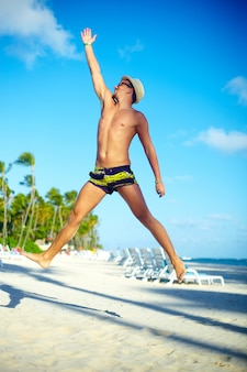 Happy handsome muscled man in sunhat on beach jumping behind blue sky behind blue sky