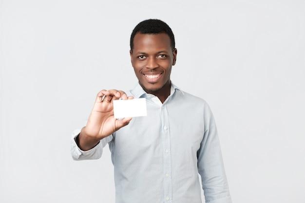 クライアントに名前カードを示す幸せなハンサムなプロアフリカ系アメリカ人実業家
