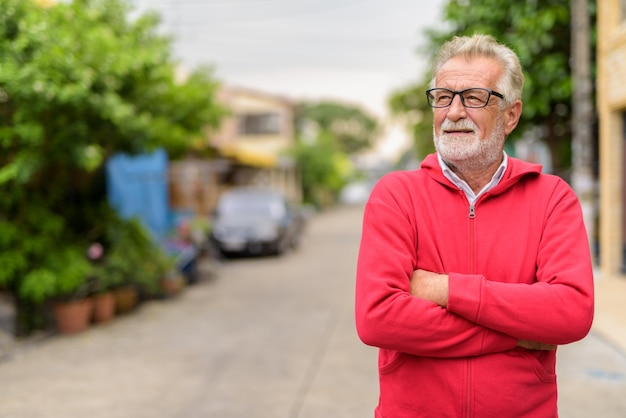 Happy handsome senior bearded man smiling and thinking while wearing eyeglasses with arms crossed outdoors