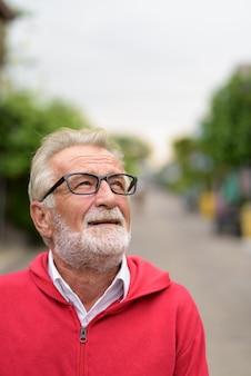 Счастливый красивый старший бородатый мужчина улыбается, думая и глядя в очки на открытом воздухе