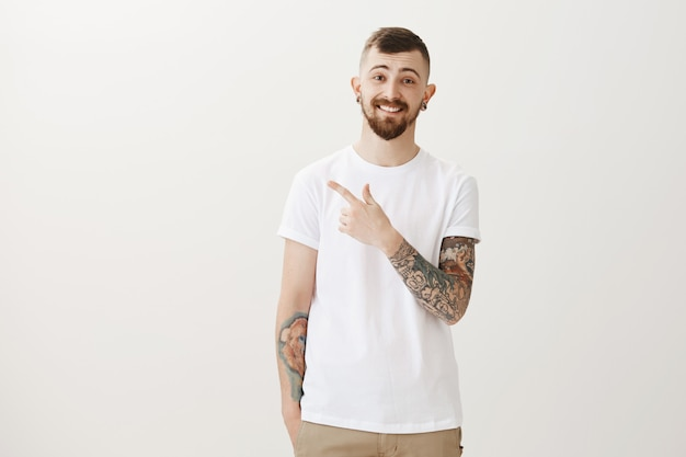 Happy handsome tattood guy pointing upper left corner and smiling satisfied