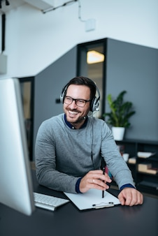 Happy handsome tech manager talking with client on headset.