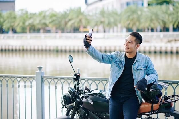 バイクに立って、ヘルメットを脱いで、自分撮りをしている幸せなハンサムなベトナム人男性