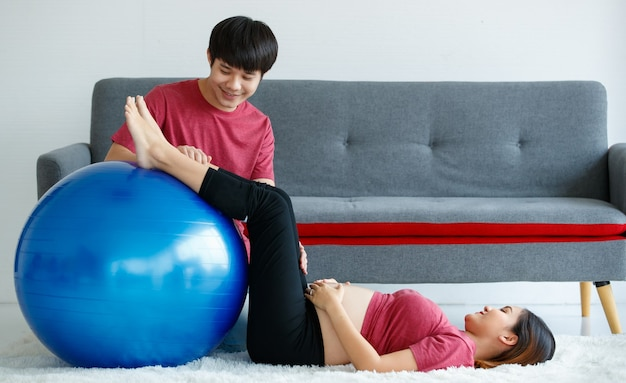 Happy handsome young asian man sitting looking at a pregnant woman happily. active husband encourages his wife to do exercise with a pilates ball at home.