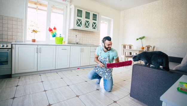 Happy handsome young beard man is cleaning the floor in the domestic kitchen and have fun.