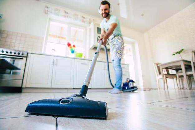 幸せなハンサムな若いあごひげの男は、家庭の台所の床を掃除して楽しんでいます。