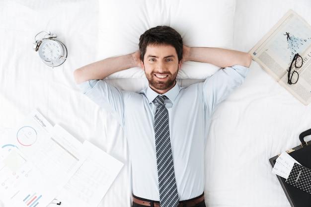 Счастливый красивый молодой бизнесмен утром в постели лежит