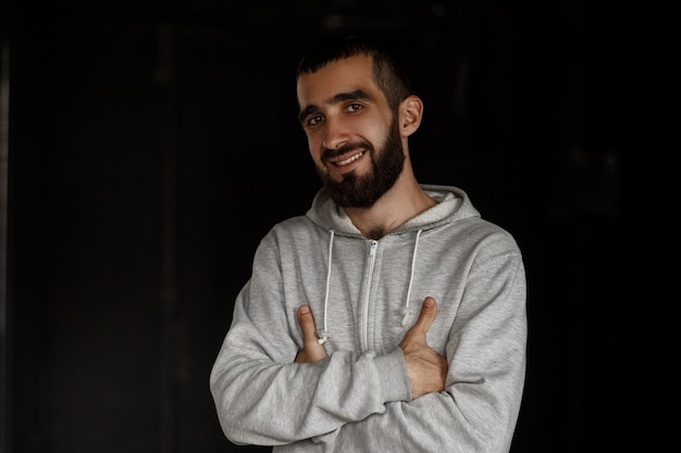 Happy handsome young guy with a beard smiling in a gray hoodie posing on a dark wall