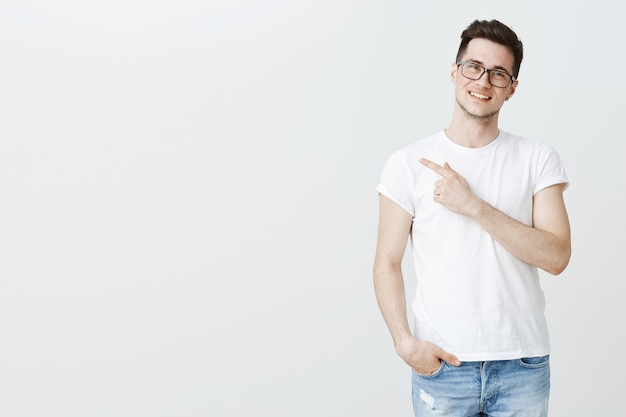 Happy handsome young male student in glasses pointing finger left at copyspace
