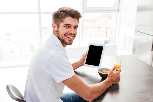 아침을 먹고 집에서 빈 화면 태블릿을 사용하는 행복한 미남