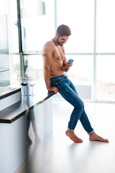 キッチンで携帯電話を使用してジーンズで幸せなハンサムな若い男