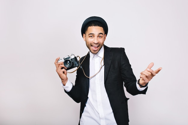 スーツ、カメラを楽しんで帽子で幸せなハンサムな若い男。ファッショナブルな外観、モダンな写真家、観光客、週末、レジャー、旅行、前向きな感情を表現します。