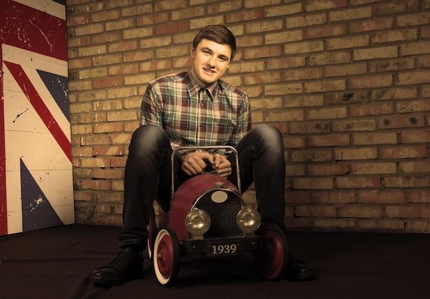 カメラを見ながらヴィンテージおもちゃの車に座って幸せなハンサムな若い男。