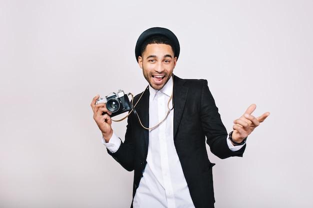 Felice bel giovane in vestito, cappello divertendosi con la fotocamera. look alla moda, fotografo moderno, turista, weekend, tempo libero, viaggi, espressione di emozioni positive.