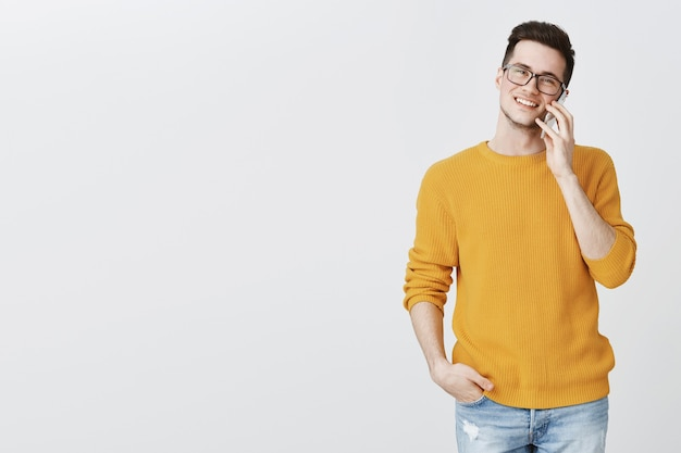 Happy handsome young man talking on phone and smiling