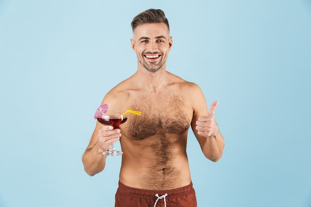 Happy handsome young shirtless man wearing beach shorts standing over blue, drinking cocktail