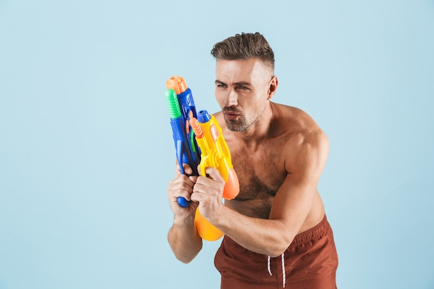Happy handsome young shirtless man wearing beach shorts standing over blue, playing with water guns