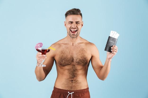 青の上に立って、カクテルを飲み、チケットとパスポートを見せてビーチショーツを着て幸せなハンサムな若い上半身裸の男