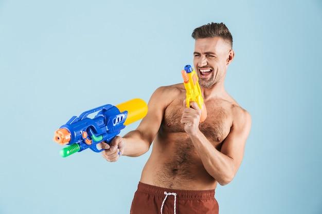 파란색 위에 서있는 해변 반바지를 입고 행복 잘 생긴 젊은 벗은 남자, 물총을 가지고 노는