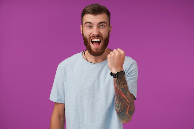 Happy handsome young tattooed brunette man with beard keeping raised fist and shouting cheerfully while posing on purple in casual clothes