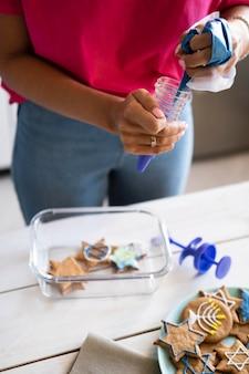 Счастливая женщина праздника хануки делает печенье