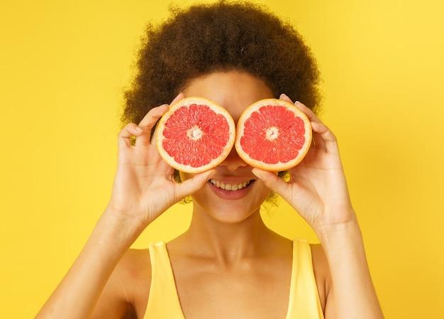 행복한 행복한 소녀는 붉은 오렌지 조각을 가지고 노는다
