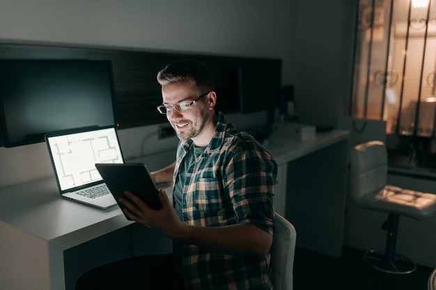Happy hardworking employee using tablet and laptop while sitting in office late at night