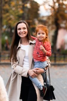 Концепция счастливой гармоничной семьи. молодая дочь матери и ребенка с рыжими волосами, вместе обниматься и радостно смеяться, отдыхая в парке на летних каникулах. семейный образ жизни на открытом воздухе.