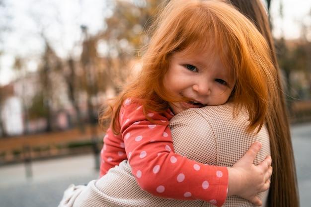 Концепция счастливой гармоничной семьи. молодая дочь матери и ребенка с рыжими волосами, вместе обнимая и радостно смеясь, отдыхая в парке во время летних каникул. семейный образ жизни на открытом воздухе.
