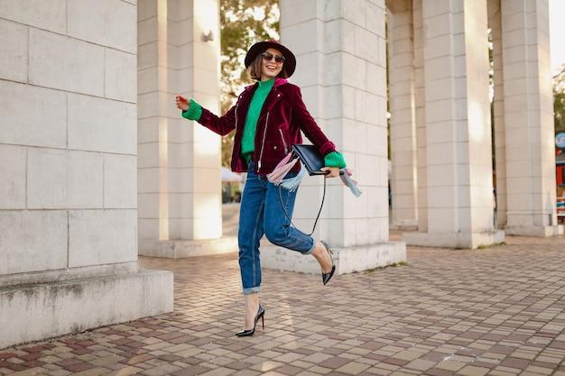 Felice divertirsi donna in abito alla moda stile autunnale che cammina per strada