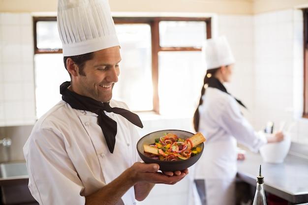 Happy head chef presenting his food