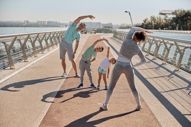 Счастливая здоровая и спортивная семья тренируется в солнечный день