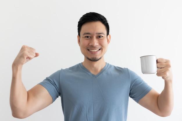 幸せな健康なアジア人男性は、隔離されたスペースで健康的なコーヒーを飲みます。