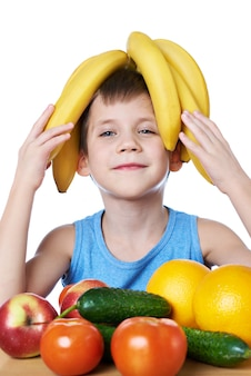 Happy healthy boy with bananas and fruits isolated