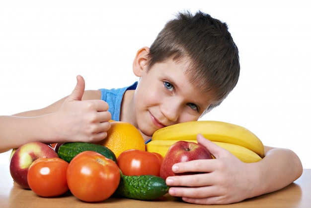 Happy healthy boy with fruits and vegetables isolated