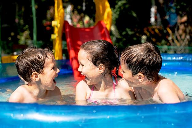 Счастливые здоровые дети летом плавают в бассейне и смеются