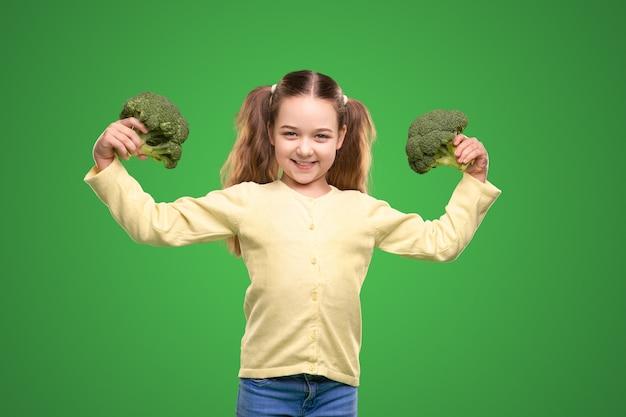 Счастливый здоровый ребенок демонстрирует зеленую брокколи