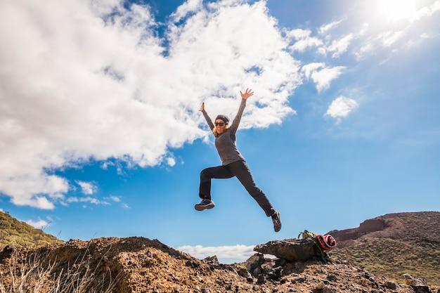 Счастливая женщина здорового образа жизни улыбается и прыгает в горы, развлекаясь в походах, приключениях - свобода и независимость для людей в природном парке под открытым небом