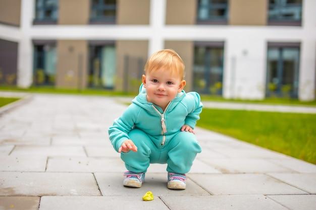 Счастливая здоровая милая девочка в синем комбинезоне веселится в городе, активный ребенок в холодный день на открытом воздухе