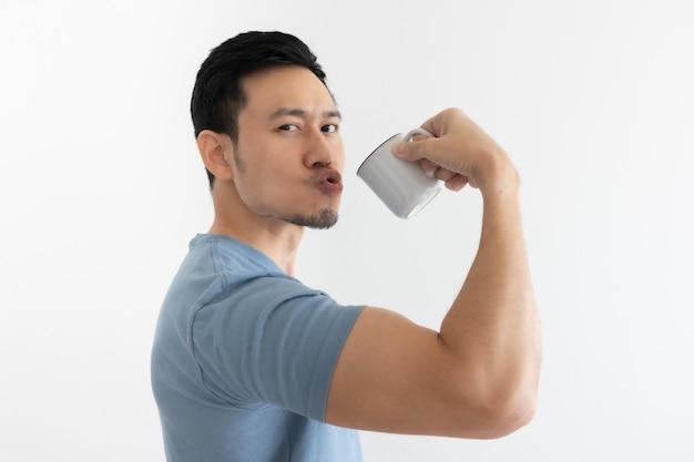幸せな健康な人は、孤立した壁に健康的なコーヒーを飲みます。
