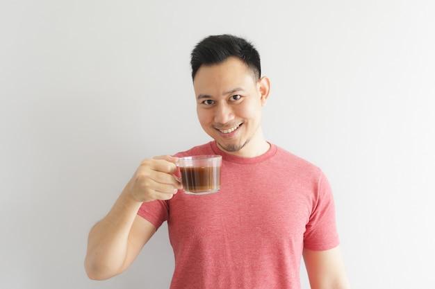 Счастливый здоровый человек в красной футболке пьет кофе или азиатские травы пить.