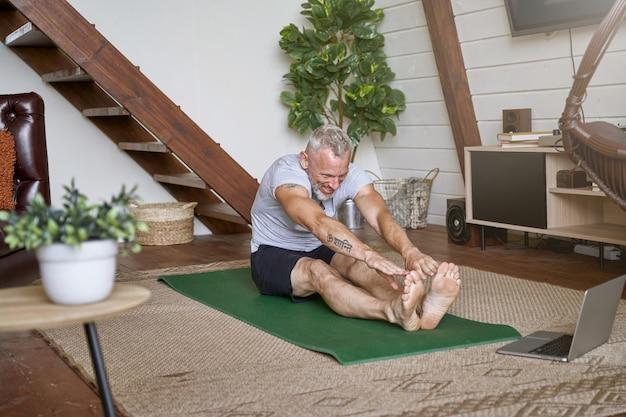 Счастливый здоровый мужчина средних лет делает упражнения на растяжку дома во время просмотра онлайн-видео