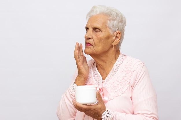 행복한 건강한 노년 여성은 얼굴에 노화 방지 보습 화장품 크림을 바르고 웃고, 스튜디오 배경에 격리된 부드러운 깨끗한 피부 관리 천연 미용 치료 로션을 웃고 있습니다.