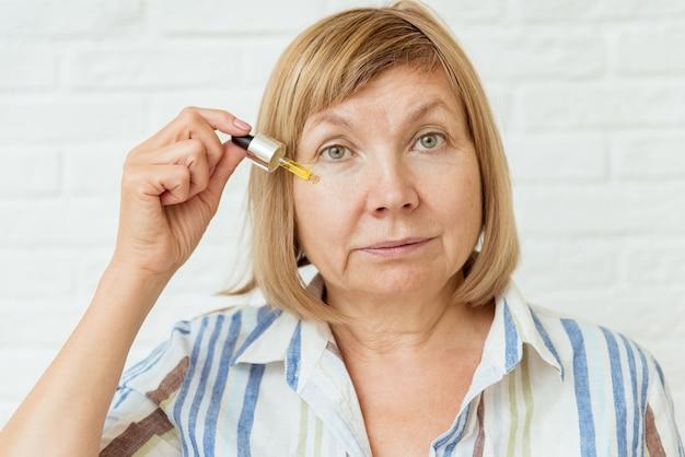 Счастливая здоровая старая старшая зрелая женщина, держащая косметическую жидкую масляную бутылку по уходу за кожей лица в руке дома, зрелая женщина среднего возраста против возрастных морщин, естественная концепция ухода за кожей красоты, вид крупным планом