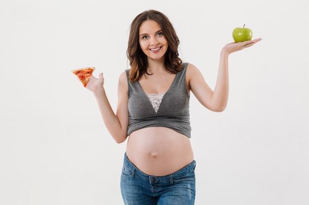 Счастливая здоровая беременная женщина выбирая между яблоком и пиццей.