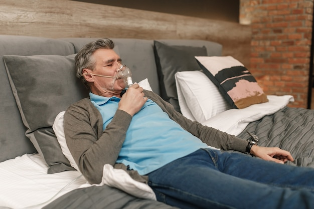Happy and healthy senior man wearing cpap mask sleeping smoothly all night long