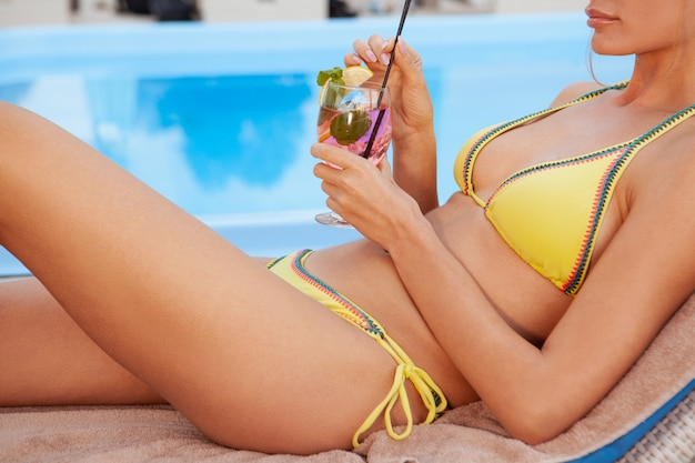 Happy healthy woman relaxing at hotel poolside