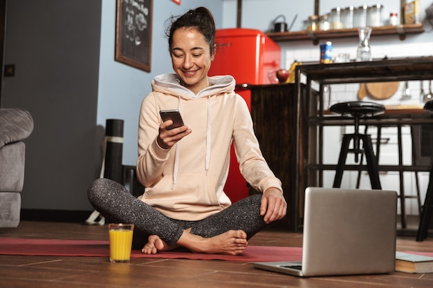 Happy healthy woman sitting on a fitness mat and talking on mobile phone at home