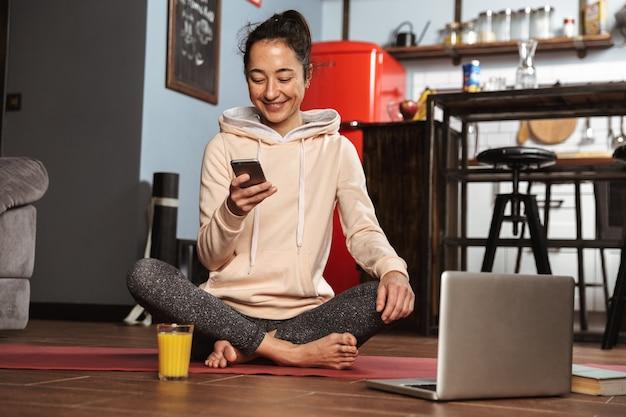 Счастливая здоровая женщина сидит на коврике для фитнеса и разговаривает по мобильному телефону дома
