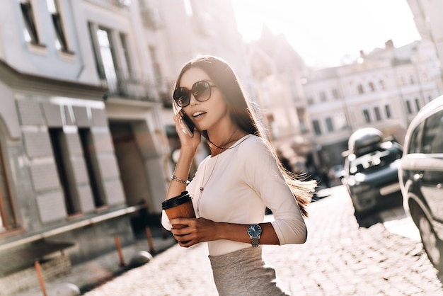 Happy to hear from you! attractive young woman talking on smart phone and looking away while walking outdoors